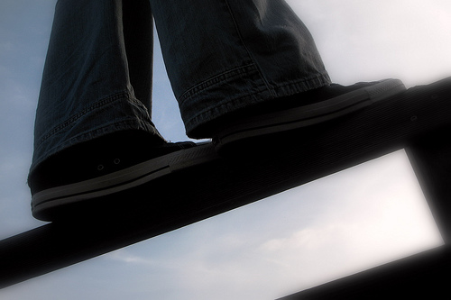 A person's shoes balancing on a beam.